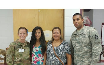 Army Reserve service members take time for photo with local community members during Operation Lone Star