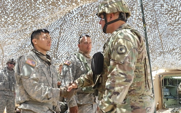 Maj. General Lee Tafanelli, the adjutant general of Kansas, presents coins to Soldiers