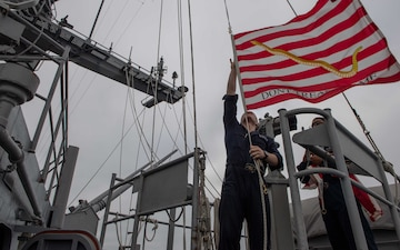 Quartermaster 3rd Class Bradley Kobernik, left, and Quartermaster 3rd Class Danaril Mojet raise the Union Jack aboard USS John C. Stennis (CVN 74).