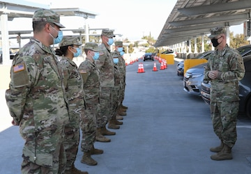 U.S. Army Col. Robert Wooldridge awards coins to Cal Guardsmen at Cal State LA vaccine site