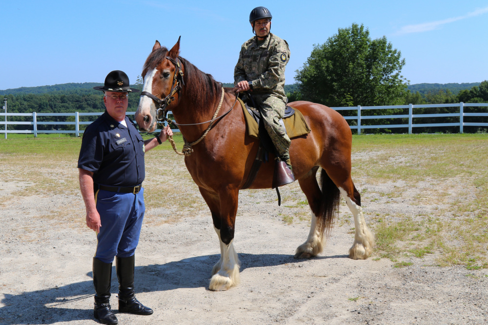 Major General Miguel Giordano, Uruguayan Defense Attaché to the US, saddles up on horse led by  Major James Marrinan, 2nd Company Governor's Horse Guard in Newtown, Connecticut